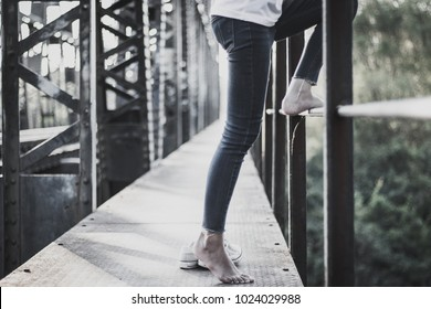 Depressed young woman and contemplating suicide, On the edge of a bridge with river below., Suicide and Major depressive disorder concept