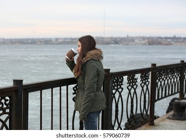 Depressed young woman drinking coffee on pier