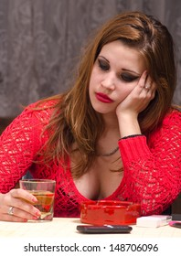 Depressed young woman drinking and smoking.
