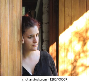 Depressed young woman leaning against door, blur