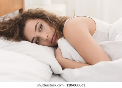 Depressed young woman lying in bed and feeeling upset after quarrel with her boylfriend in bed at home, closeup