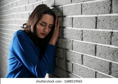 Depressed young woman near brick wall
