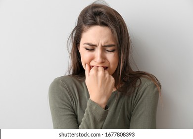 Depressed young woman on light background