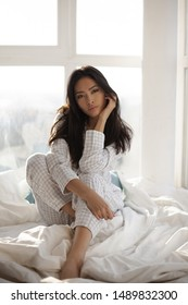 Depressed young woman sitting on bed at home. Asian young woman in nightgown dress sitting on the bed in the morning against big window. Attractive model looking at camera.