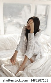 Depressed young woman sitting on bed at home. Asian young woman in nightgown dress sitting on the bed in the morning against big window.