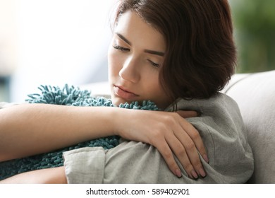 Depressed young woman sitting on sofa at home, closeup