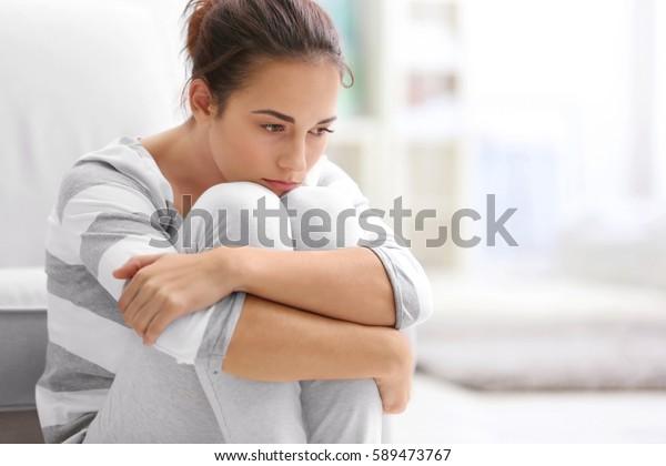 家で床に座っている落ち込んだ若い女性
