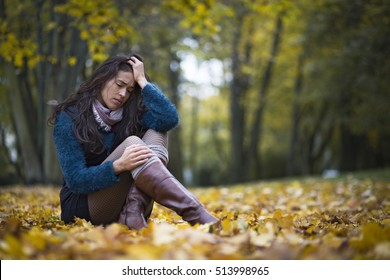Depressed young woman sitting in a park full of autumn leaves