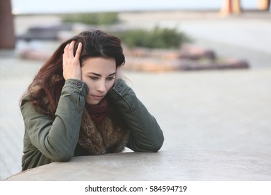 Depressed young woman sitting at table on street