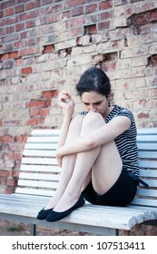 Depressed young woman smoking a cigarette outdoors in an urban area