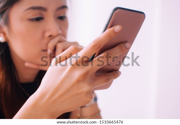 A depressed young woman is using a mobile phone