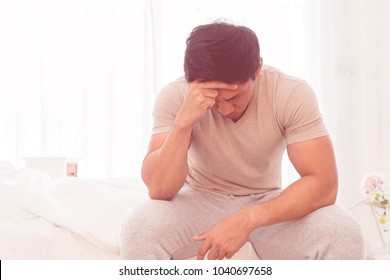 Depressing asian man is siiting on bed with headache