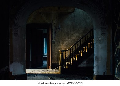 A depressing view of the foyer with a grand staircase, accented by a wood banister, flanked by cracked plaster, at a long abandoned Federal Revival styled house.