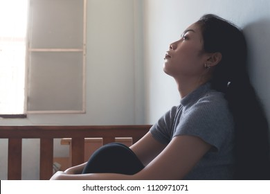 depression asian woman is sad and stress in bedroom, close up at face