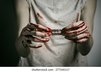 Depression and bloody Halloween theme: a man holding a bloody razor for suicide on a gray background in the studio