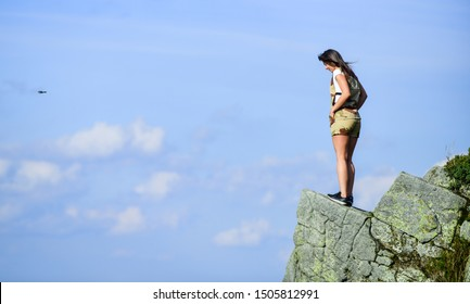 Depression concept. Brave woman stand alone in high mountains blue sky background. Soldier girl. Military female. Observing point. Brave girl dangerous cliff. Suicidal mood. Brave and fearless.