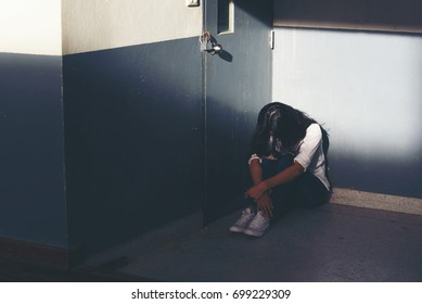 Depression concept. Lonely depressed woman cry and hug her knees sitting alone in the dark corner, Sad woman Unhappy and stressed student on the campus.With copy space