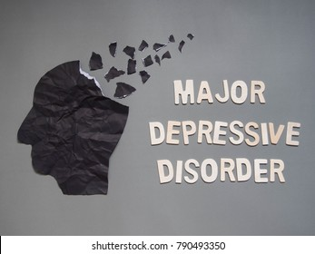 Depression or Major Depressive Disorder (MDD) presented by human head made form black crumpled paper torn on gray background. Mental health care, brain disorder and psychology concept.