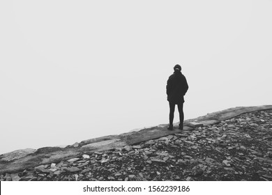 Depression (mental illness) concept image consisting of an unrecognizable woman standing on the edge of a cliff.