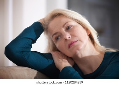 Depression. Middle aged woman barefoot sitting on the couch, hugging her head, at home. The concept of sadness and loneliness.