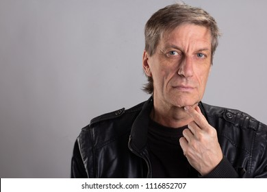 depression old adult tired a 55-year  man dressed in a black leather jacket looks at the camera gray eyes. elderly man clean-shaven, gray-haired. senior adult, left hand on chin,