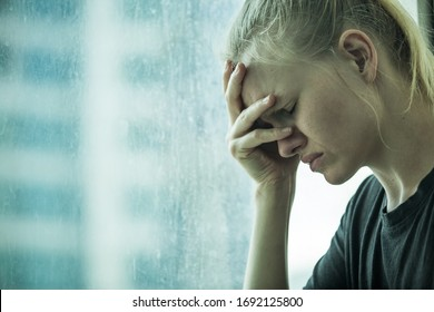 Depression and sadness. Woman crying by the window with her hand in face. Feeling heartbroken and stress.