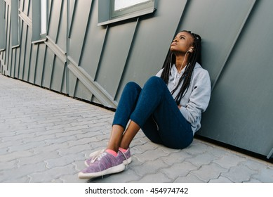 Depression teen african american girl listening to music and sitting lonely looking up at urban background