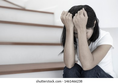 The depression woman alone sitting on staircase she thought so much and headaches, eye pain.