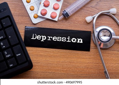 Depression words written on label tag with medicine,syringe,keyboard and stethoscope with wood background,Medical Concept