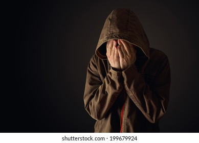 Depressive man in hooded jacket crying with hands covering his face, looking upset and showing remorse