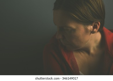 Depressive pessimistic lonely woman in dark room, low key portrait of sad adult female