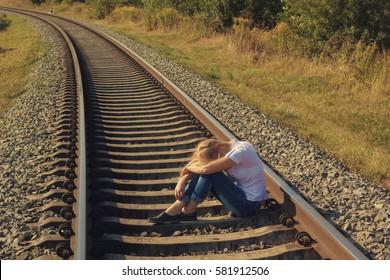 Depressive woman sitting on a railway track