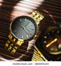 Depth close up gold watch natural sunlight on dark wood background