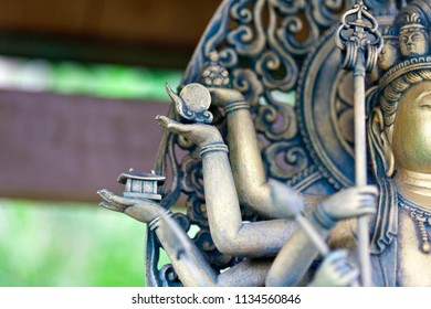 Depth of field of golden Buddha statue with many arms in a Buddhist temple in Kamakura, Japan