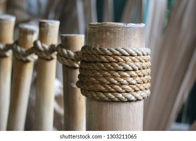 A depth of field image of sisal wound around bamboo sticks creating a fence.
