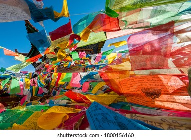 Deqen, China - 08 17 2009: colorful Tibetan Buddhist prayer flags hanging from a pagoda near Kawa Garpo mountains, home of one of Tibetan Buddhism's most sacred pilgrimages.