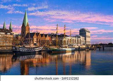 In der Dämmerung liegen Dreimaster vor der Promenade an der Weser in Bremen und spiegeln sich im Wasser - Shutterstock ID 1691152282