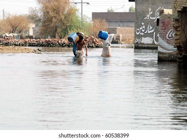 DERA ALLAHYAR, PAKISTAN-SEPT 02: Flood affected men hold cans move in search of drinking water through flood water at a flood hit area on Thursday, September 2, 2010 in Dera Allahyar, Pakistan