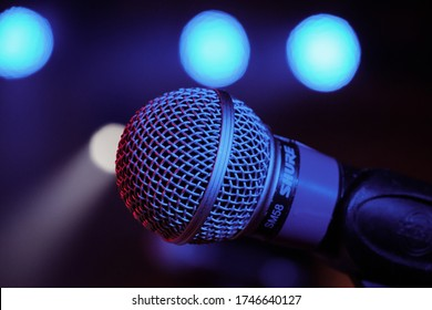 DERBY, UNITED KINGDOM - Dec 15, 2019: Shure microphone close up on stage during sound check at a live music venue. Taken under stage LED lighting