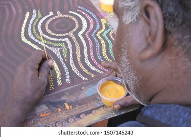 DERBY, WA - SEP 10 2019:Aboriginal artist dot painting.Before Indigenous Australian art was ever put onto canvas the Aboriginal people would smooth over the soil to draw sacred ceremony designs.