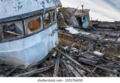 Derelict abandoned fishing boats near the harbor in Gustavus Alaska rotting in the weeds.