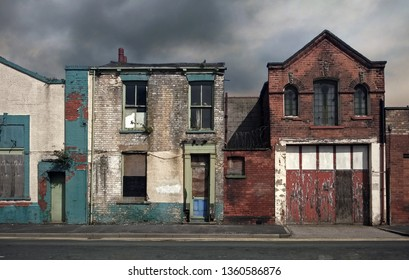 derelict abandoned houses and buildings on a deserted residential street with boarded up windows and decaying crumbling walls against a grey cloudy sky