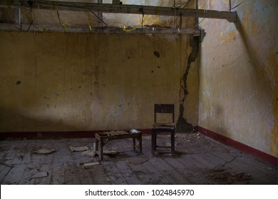 A derelict abandoned room, with water-stained peeling walls, and a broken old wood table and chair on dirty wood floorboards.