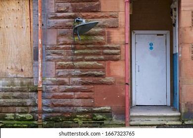 Derelict council house doorway in poor housing  estate slum with many social welfare issues in England UK