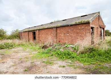 Derelict Farm Building, Abandoned agricultural red brick outbuilding with asbestos roof. In open field.