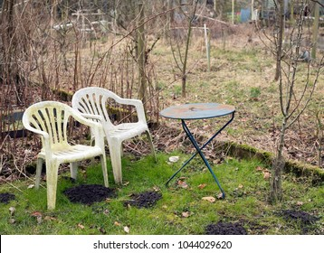 derelict garden with old plastic weathered deserted empty chairs in winter