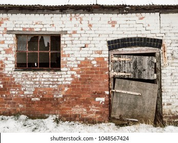 A derelict house with barn door hanging loose and a broken window, Shropshire, UK