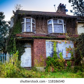 A derelict house with ivy growing over it
