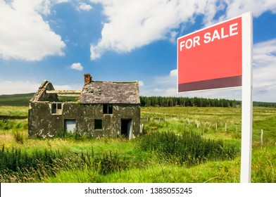 "Derelict house in a rural situation with blank ""For Sale"" sign"