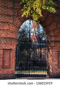 Derelict ruins of the Columbia State Mental Hospital in Columbia, South Carolina, sits behind locked, black metal gate.  Arched opening in brick wall gives peek to closed facility.